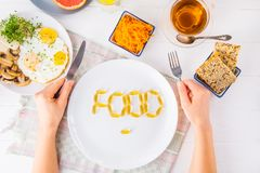 Top view female hands holding knife and fork and white plate with Food lettering by vitamin pills on the served wooden table with. Breakfast meal. Pill instead Royalty Free Stock Images