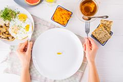 Top view female hands holding knife and fork and white plate with vitamin pill on the served wooden table with breakfast meal. Pil. L instead of food. Healthy Royalty Free Stock Photography