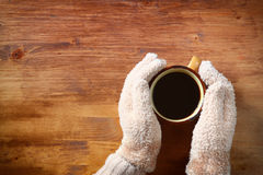 Top view of Female hands with a hot coffee, on wooden background. Royalty Free Stock Photo