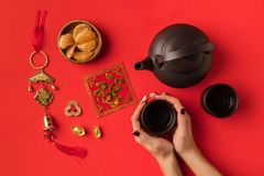 Oriental decorations and tea set. Top view of female hands, oriental decorations and tea set isolated on red Stock Image