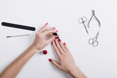 Top view of female hands painted nails with red lacquer. Lie on white table accessories for manicure Stock Images