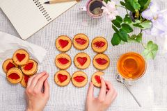 Top view female hands playing tic tac toe game by cookies with hearts and kiss shapes on white table with tea and coffee cups, not stock photos