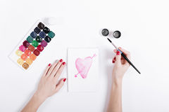 Top view of a female hands with red manicure draw the watercolor Royalty Free Stock Photo