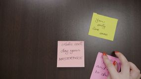 Top view of female hands sticking handwritten post it notes that contains motivational quotes on her dark wooden desk at work -. Top view of female hands stock footage