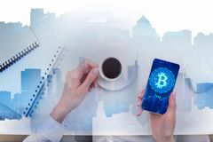 E-commerce and finance concept. Top view of female hands using smartphone with bitcoin and holding coffee cup at abstract white desk with notepad and city stock images