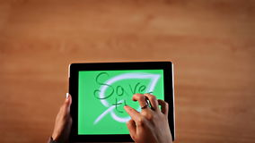 Top view female hands writing Save the planet, calligraphy on digital tablet stock footage