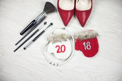 Top view female items 2018 new year. Flat lay female accessories for New Year top view on white wood background: red festive shoes, make up brushes, mittens Stock Photo