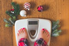 Top view of female legs in pajamas on a white weight scale with Christmas decorations and lights on wooden background. Top view of a female leg in red, white and royalty free stock photography