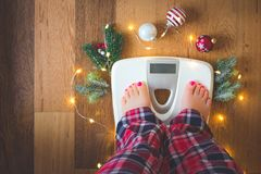 Top view of female legs in pajamas on a white weight scale with Christmas decorations and lights on wooden background. Top view of a female leg in red, white and royalty free stock image