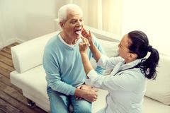 Top view on female nurse checking tonsils of senior patient. Regular checkup. Mature doctor using a medical stick while sitting on a sofa and checking throat and royalty free stock images