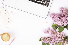 Top view of female worker desktop with laptop, flowers and different office supplies items. Feminine creative design workspace. Feminine desktop close up stock photos