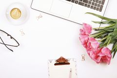 Top view of female worker desktop with laptop, flowers and different office supplies items. Feminine creative design workspace. Feminine desktop, close up of royalty free stock photography