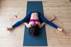 Top view of female yogi doing advanced kurmasana tortoise pose on mat indoors while practicing yoga Stock Photo