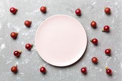 Top view of festive plate with red baubles on cement background. Christmas decorations and toys. New Year advent concept