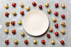Top view of festive plate with red and golden baubles on cement background. Christmas decorations and toys. New Year advent