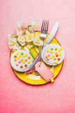 Top view of festive table place setting with cake, Narcissus flowers, cutlery and blank tag on pastel pink background, top view. Easter or spring table setting stock photos