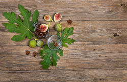 Top view of figs on fig leaf and jam  on wooden table Royalty Free Stock Image
