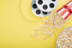 top view of film coils near buckets with popcorn on yellow, cinema concept.