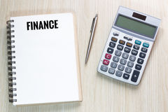 Top view of Finance wording on notebook with calculator and pen Royalty Free Stock Images