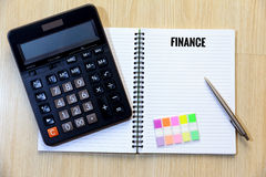 Top view of Finance wording on notebook with calculator, pen and Stock Photos