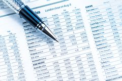 Top of view of financial business pen on currencies newspaper Stock Photos