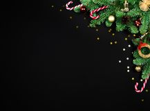 Top view fir frame, Christmas tree branch border, festive decor, stars confetti layout with copy space on black