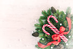 Top view of a fir tree and candy cones tied with a red bow over an old white wood background. Christmas decoration background. Vin Royalty Free Stock Photography