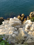 Top view of fisherman sitting on rocks with fishing rods Stock Photography