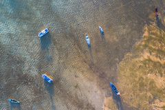 Yellow sky during sunrise above fishing boats in Rawai sea. Top view fishing boats in the shore during low tide at Rawai beach Phuket Thailand royalty free stock image