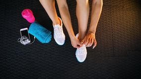 Top view of a fit woman seated on the floor of a gym tying shoelaces sneakers. Healthy lifestyle. Sport and cardio workout concept stock video footage
