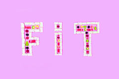 Fit word made of colorful sweets isolated on pink Stock Image