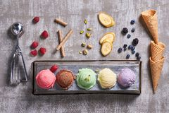 Top view of five colorfull icecream balls with pistachios,banana slices,chocolate sticks,raspberries, blueberries, waffle cones stock photos