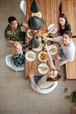 Top view of five people cheering with wine. While sitting at the rustic dining table and looking up at camera Stock Images