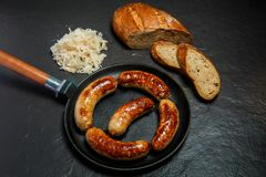 Top view five tasty ruddy juicy sausages fried in large pan. Served with sliced rye bread and sauerkraut on black background royalty free stock photo