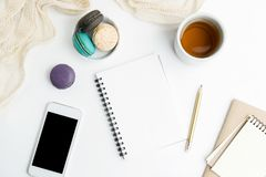 Top view flat lay blank notebook and cell phone mockup with macarons and tea cup. Art, writing concept. Text space stock photo