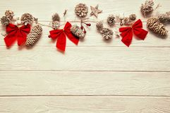 Christmas textural wooden background. Traditional stylized garland with small and big fir cones, red bows and stars. stock photography