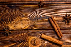 Cinnamon sticks and star-shaped anise are located on a brown wooden boards. royalty free stock images