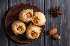 Top view, flat lay. Close up. Turkish traditional sweets on an old clay saucer. Baklava bird`s nest. Dark wooden background royalty free stock image