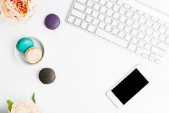 Top view flat lay colorful macarons with keyboard, cell phone and pink peonies on white table. Creative dessert concept. Text space stock photo