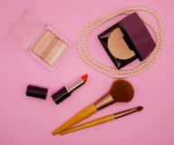 Flat lay cosmetics and brush on pink background stock image