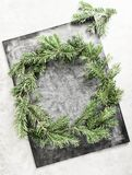 Top view flat lay green Christmas wreath on chalkboard covered with white chalk. Traditional New year decoration concept. Space for lettering royalty free stock image
