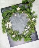 Top view flat lay green Christmas wreath on chalkboard covered with white chalk. Traditional New year decoration concept. Space for lettering royalty free stock photos