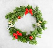 Top view flat lay green Christmas wreath with toys and red bows on bright background. Traditional New year decoration concept. Space for lettering royalty free stock images