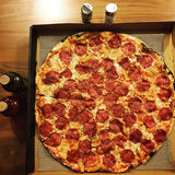 Top view flat lay of a large thin crust Pepperoni pizza with accompaniments Royalty Free Stock Photography