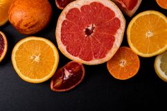 Top view, flat lay, macro. Sliced citrus fruits on a black background