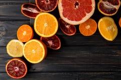 Top view, flat lay, macro. Sliced juicy oranges, tangerines, grapefruit. Dark background. Copy space royalty free stock photography