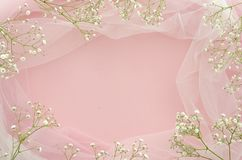 Flat lay wedding concept. Frame made of gypsophila and white tulle on pink background with copy spase for your text