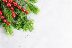 Top view flat lay natural Christmas tree branches with red toys, bow and glass reindeer corner frame on bright background. New yea. R decor concept. Text space stock images