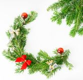 Top view flat lay natural Christmas tree branches with red toys, bow and glass reindeer corner frame on bright background. New yea. R decor concept. Text space royalty free stock image