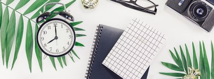 Top view flat lay office workspace desk styled design office supplies alarm clock tropical palm leaves smartphone camera copy. Space black white background stock photo